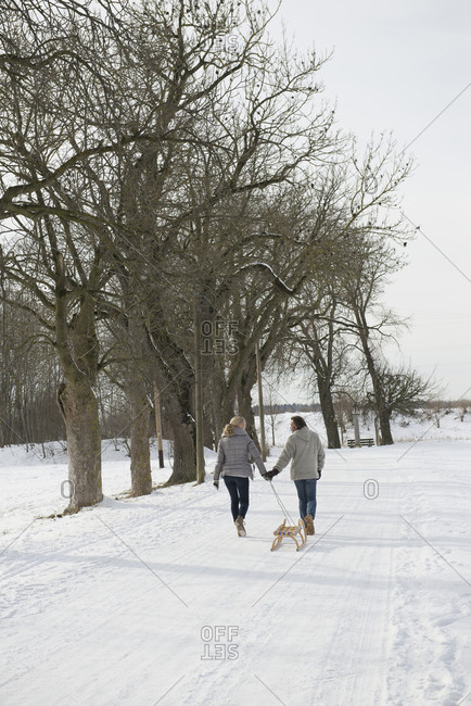 Couple pulling sledge in snow