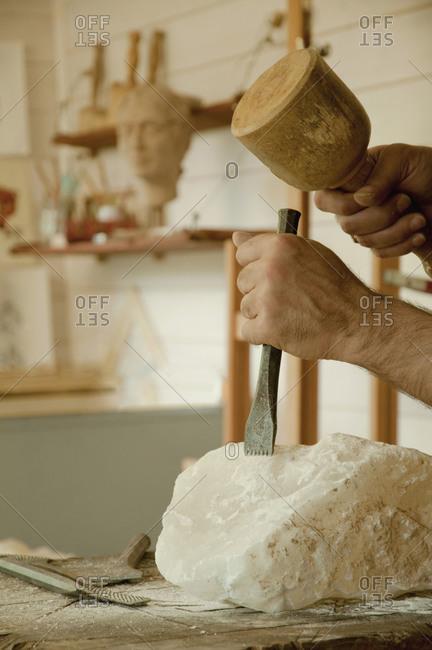Mature man carving soapstone