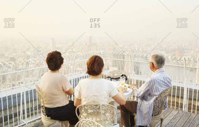 Rear view of Asian people watching a panorama from a terrace