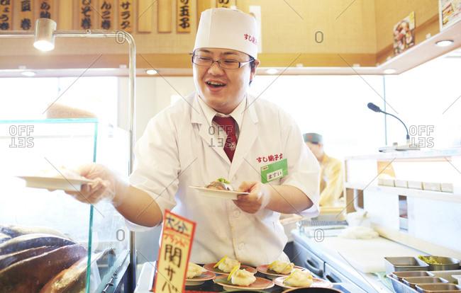 Yokohama, Japan - July 25, 2014: Sushi chef serving mackerel