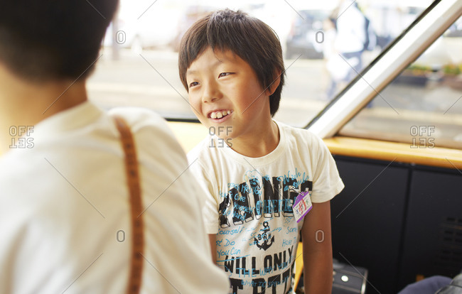 Japan - July 30, 2014: Boys riding the train from Kagoshima to Aso, Japan while on summer vacation