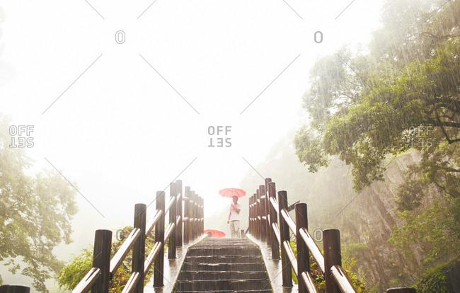 Man with umbrella near Takachio natural waterfalls