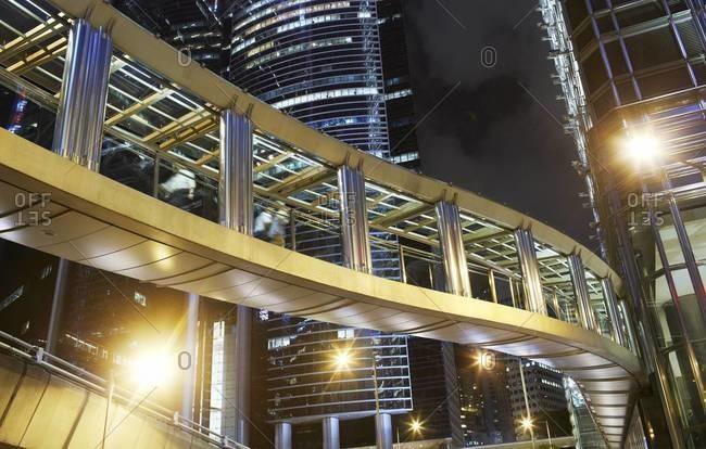 People crossing on a footbridge in Hong Kong at night