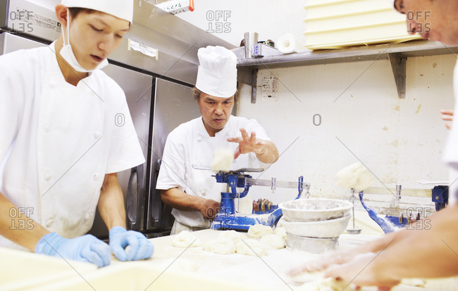 Kanagawa, Japan - August 13, 2014: Chefs kneading dough in a kitchen