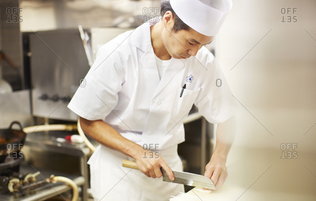 Tokyo, Japan - August 14, 2014: Japanese chef slicing daikon in the Akihabara district