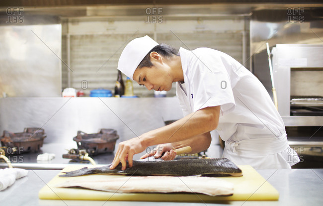 Tokyo, Japan - August 14, 2014: Japanese chef preparing fish in the Akihabara district