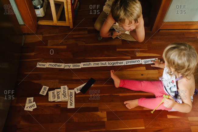 Children playing a word game on the floor