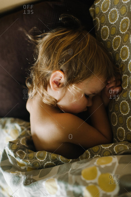 Portrait of a young girl sleeping in a bed