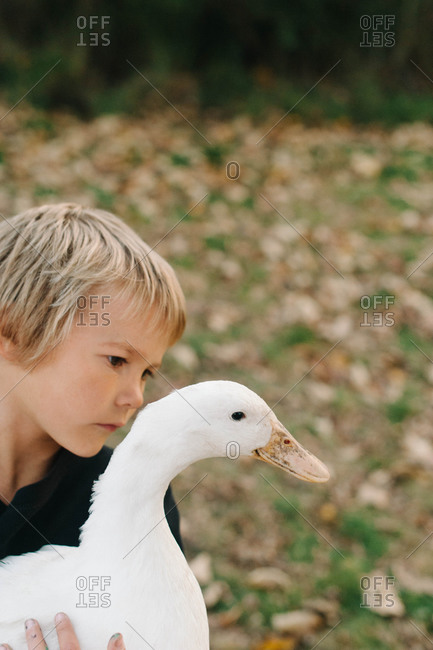 Portrait of a young boy with a goose