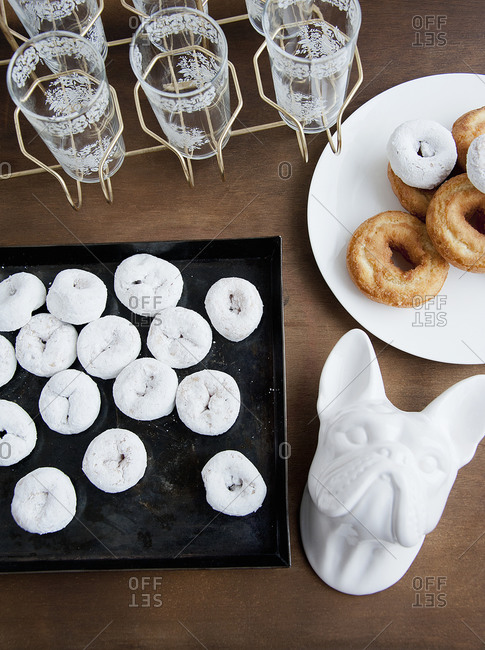 Tiny white donuts lay on a tray next to other objects