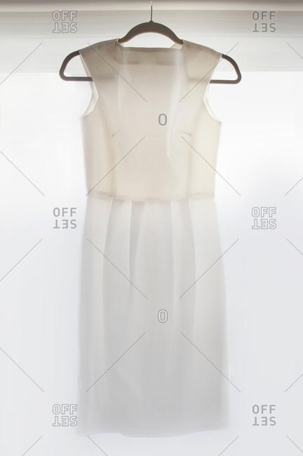 A dress hangs in front of a window
