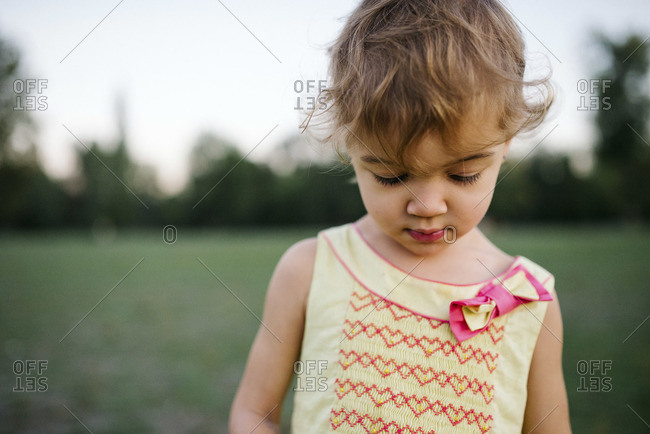 A young girl wanders through a field