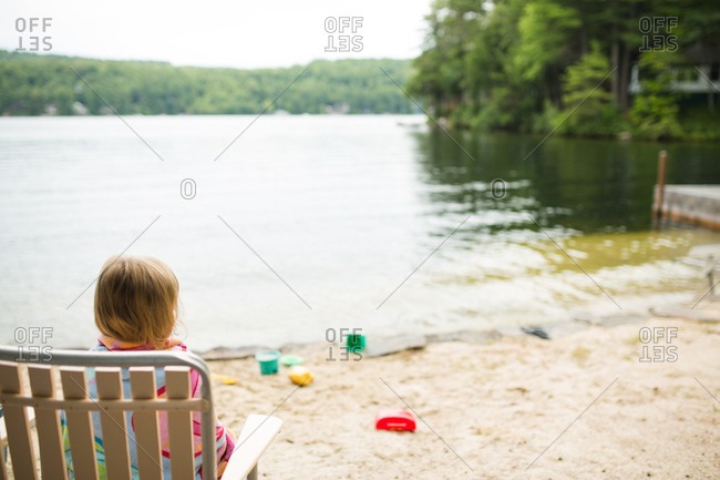 Young girl sitting on a chair at the beach