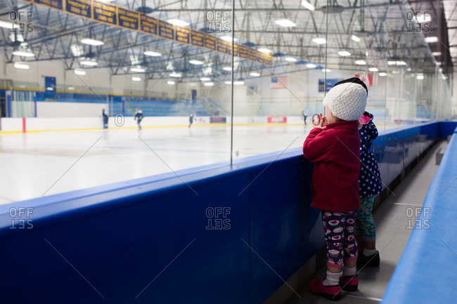 Young girls looking at a hockey training in an ice rink