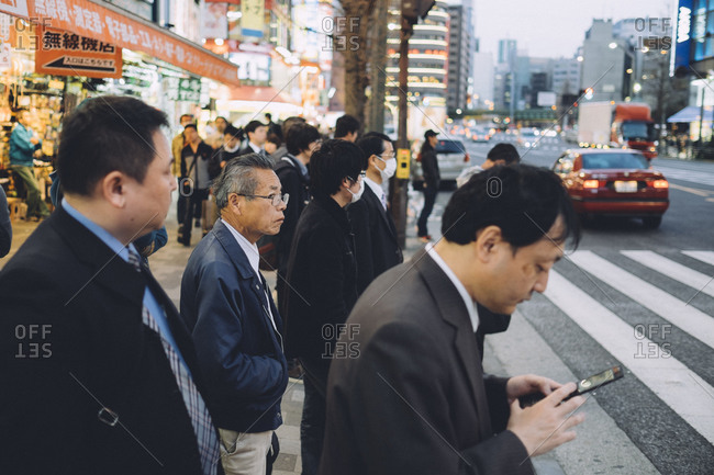 Tokyo, Japan - April 1, 2014: Men stand on a corner waiting to cross the street