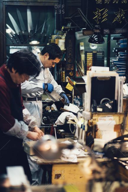 Tokyo, Japan - April 1, 2014: Two men work manufacturing knives