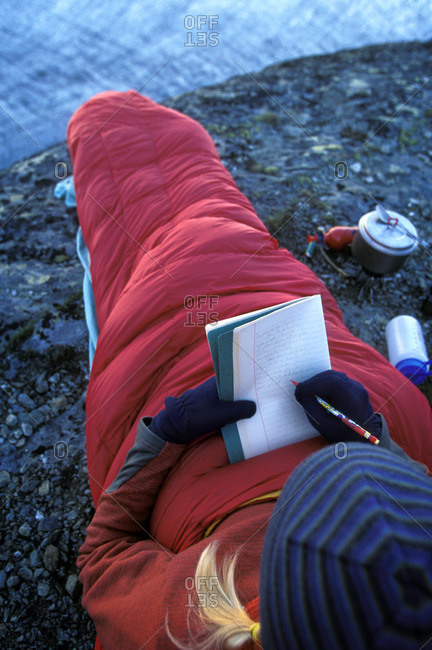 Woman writing in journal while laying in sleeping bag in backpacking camp