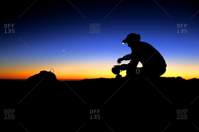 Backpacker cooking on camp stove and using headlamp at sunset