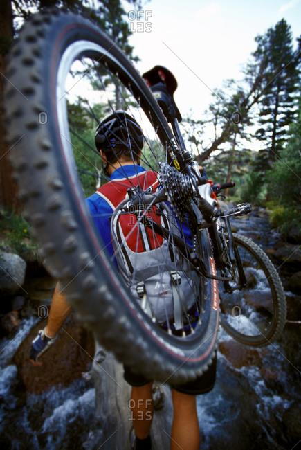 Mountain biker carry bike on shoulder while crossing log over creek, California, USA