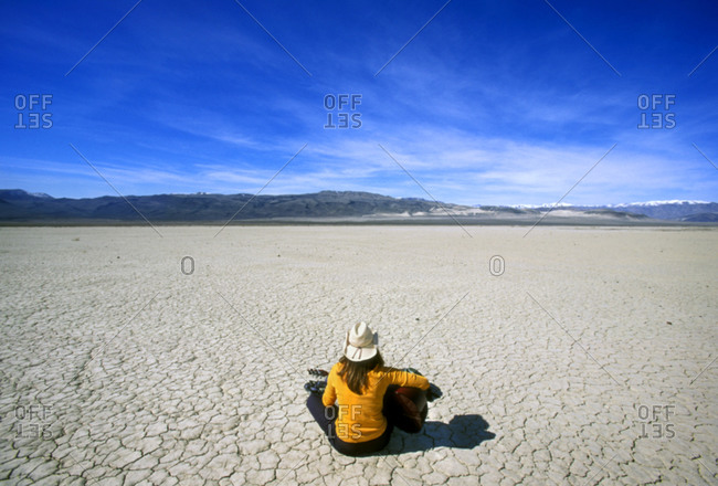 Woman playing guitar alone in the vast Death Valley desert landscape, USA