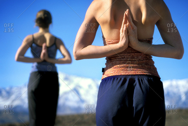 Two women in yoga pose with hands behind their backs, Owen's Valley, California
