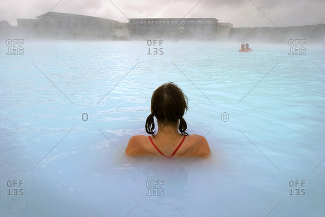 Rear view of woman relaxing in The Blue Lagoon hot spring, Iceland