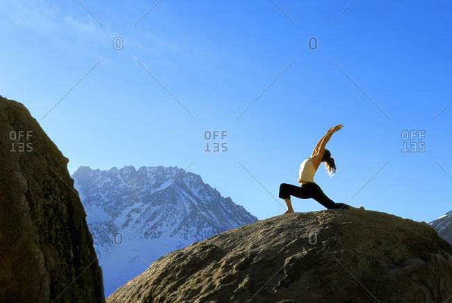 Woman doing Warrior Pose  on boulder