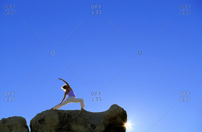 Low angle view of a woman practicing yoga on a cliff
