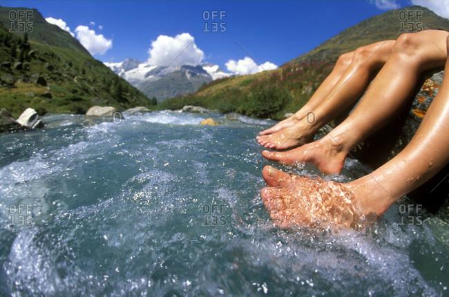 Two women dangling feet in mountain creek, Switzerland