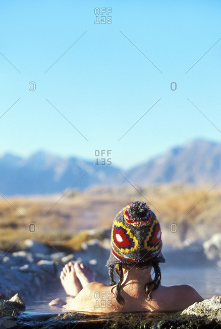 A woman sitting in hot spring watching the early morning light, Eastern Sierra region, USA