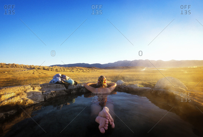 Woman resting in hot spring watching the landscape, Eastern Sierra region, USA
