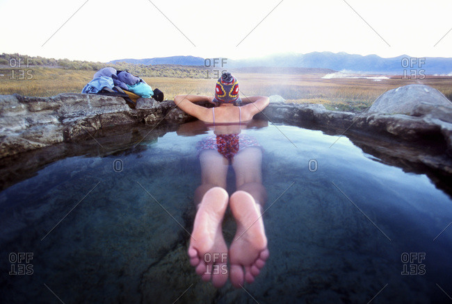Back view of woman lying in hot spring, California, USA