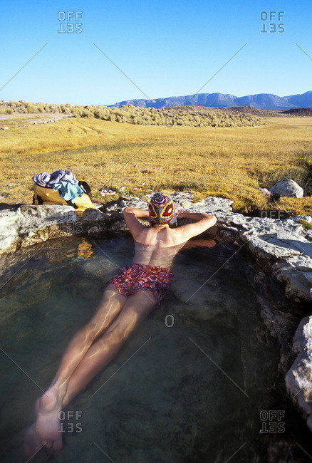 Relaxed woman lying in hot spring, Eastern Sierra, USA
