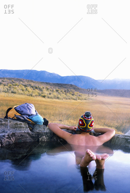 Lone woman sitting in an open air hot spring, California, USA