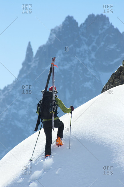 Skier ascending snow ridge on Aiguille du Brevent with skis strapped to backpack, France