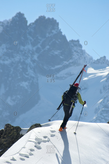 Skier ascending snow ridge on Aiguille du Brevent with skis strapped to backpack, Chamonix, France