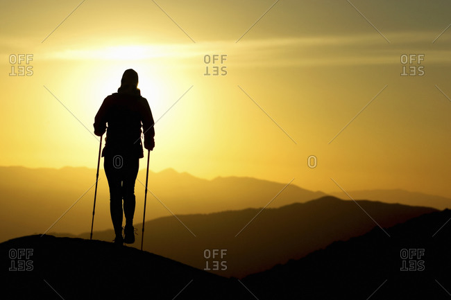 Lone backpacker's silhouetted figure hiking with the sun low on the horizon behind
