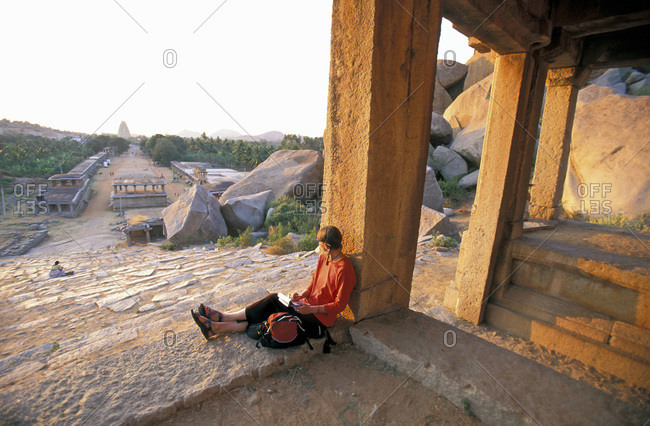 Woman sitting in Temple, writing notes and watching sunset over the small Indian town of Hampi