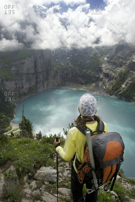 Female hiker overlooking the Oeschinen Lake, a small glacier lake, Switzerland