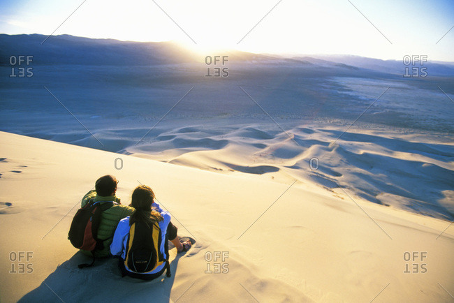 Couple sitting in sand dunes watching the sunset, California, USA
