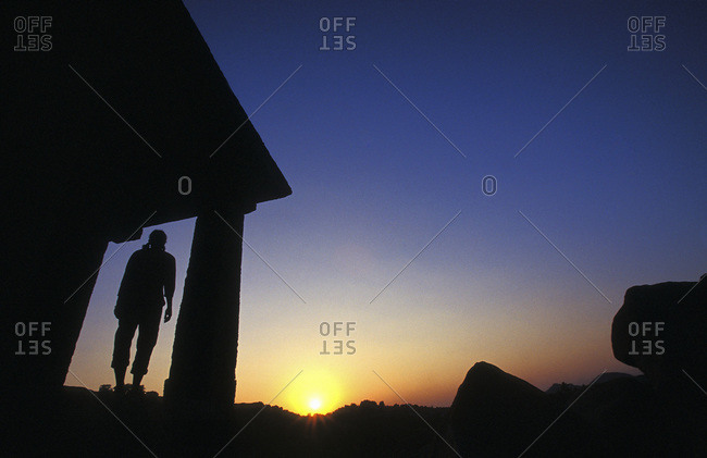 Silhouette of a woman at sunset in the small village of Hampi, India