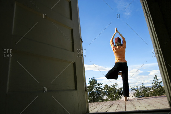 Woman practicing yoga tree pose on the deck of a small cabin in Bishop, USA