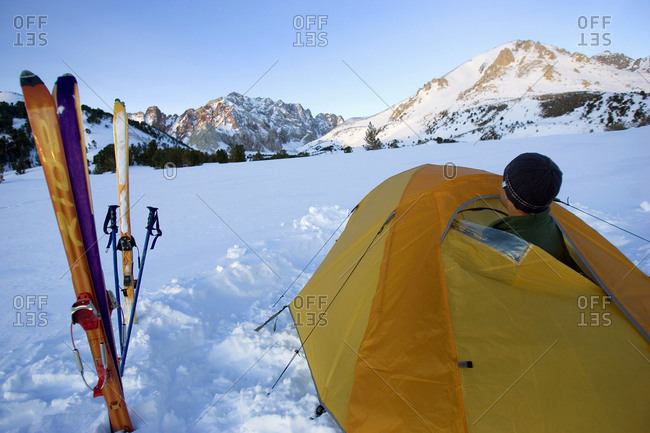 Skier looking outside of a tent in Sierra Nevada, USA