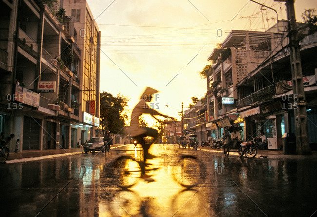 Cyclist crossing a street after a heavy rainfall in Can Tho, Vietnam