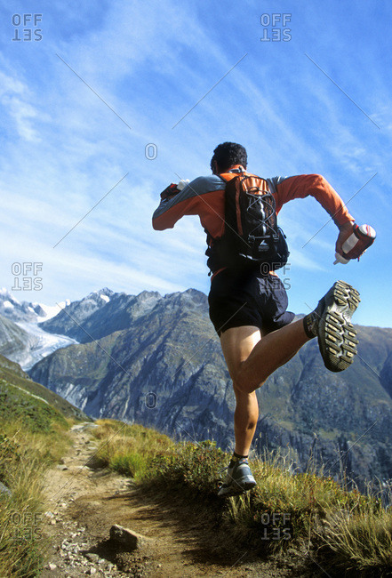 Trail runner running on the Aletchgletcher Trail in Bettmeralp, Switzerland