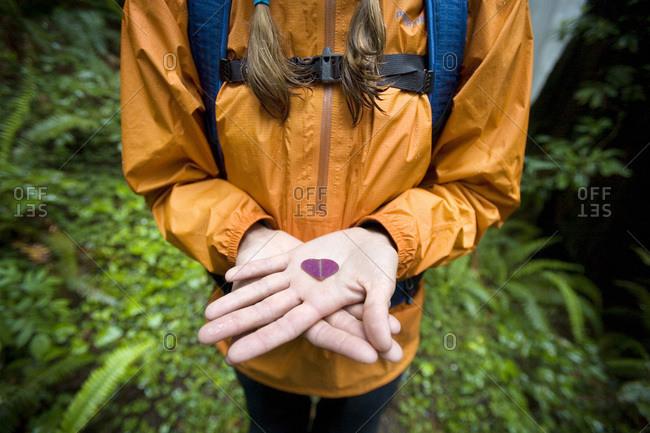 Woman holding heart shaped leaf