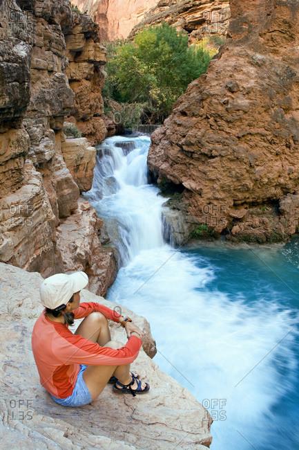 Woman hiker looking at Havasu Canyon's waterfalls