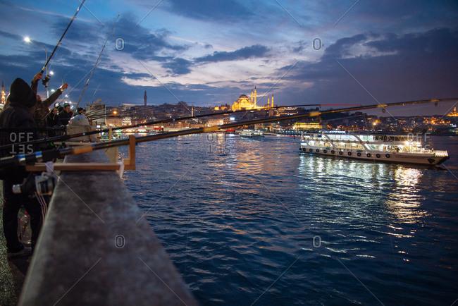 Istanbul, Turkey - February 8, 2014: People fishing off the Galata Bridge