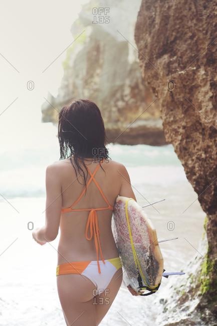 Rear view of brunette woman with bodyboard