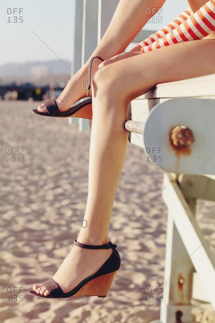 Woman putting on a high heel sandal on a beach